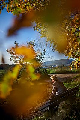 Frau sitzt auf einer Bank bei schönem Herbstwetter - p227m1503295 von Uwe Nölke
