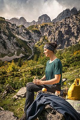 Woman on a hiking trip at Wilder Kaiser having a break, Kaiser mountains, Tyrol, Austria - p300m2166838 by Manuel Sulzer