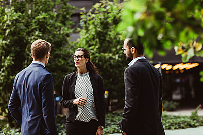 Female and male entrepreneurs discussing business strategy while standing outdoors - p426m2170232 by Maskot