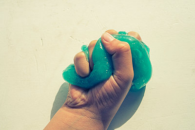 Close up of a child squeezing slime  - p794m2057309 by Mohamad Itani