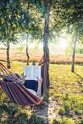 Woman in hammock reading a book - p879m2257751 by nico