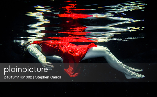 Woman in red dress floating underwater - p1019m1461902 by Stephen Carroll