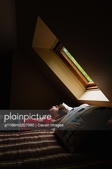 Young boy laying on bed looking up through a sky light in a dark room. - p1166m2207990 by Cavan Images