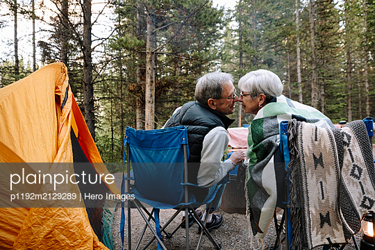 Affectionate senior couple kissing at campsite - p1192m2129289 by Hero Images
