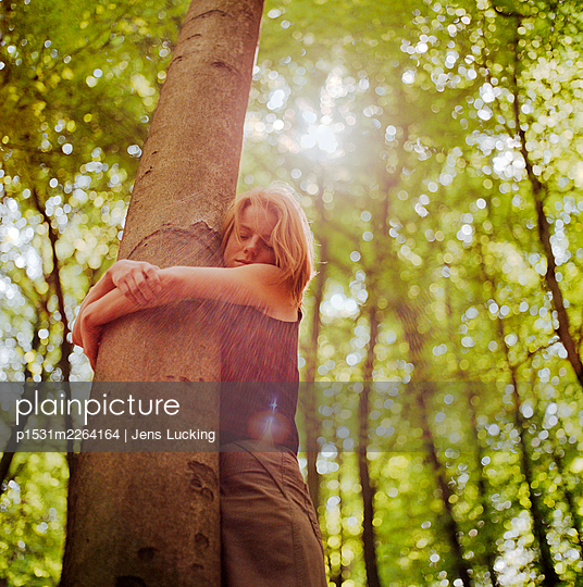 Red Haired Woman Hugging Tree In Forest, Eyes Closed - p1531m2264164 by Jens Lucking