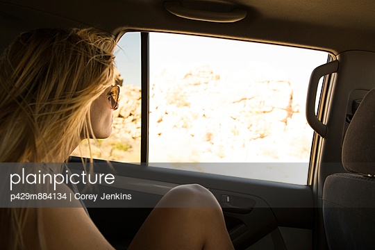 Young woman looking out of back seat car window - p429m884134 by Corey Jenkins