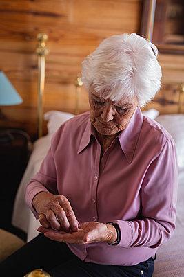 Active senior woman taking medicine in bedroom at home - p1315m2091083 by Wavebreak