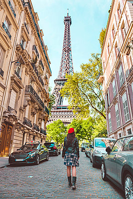 France, Paris, Eiffel Tower among the buildings, nearby street and woman wearing a red beret walking on the street - p300m1153428 by Gemma Ferrando