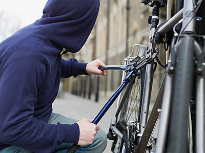 A thief stealing a bike - p9247280f by Image Source