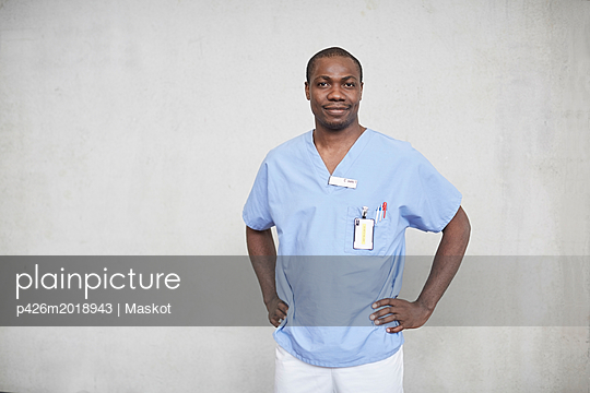 Portrait of confident mid adult male nurse standing with hands on hips in corridor at hospital - p426m2018943 by Maskot