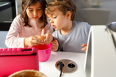 Curious boy by sister breaking egg in mixing bowl at kitchen counter - p300m2265777 by Ignacio Ferrándiz Roig
