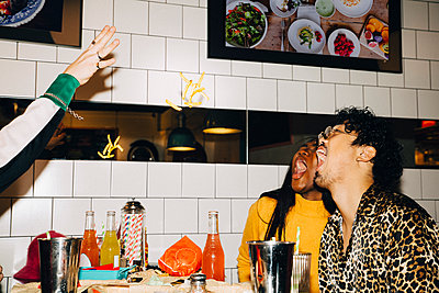 Cropped hand of man throwing french fries at male and female friends with open mouth in cafe - p426m2194762 by Maskot