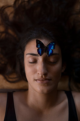 Blue butterfly on forehead of young woman - p552m1468185 by Leander Hopf