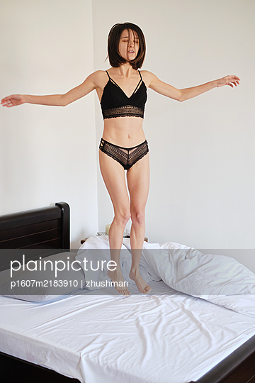 Young brunette woman jumping in her bed at morning - p1607m2183910 by zhushman
