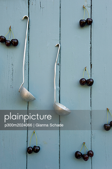 Cherries and two laddles hanging on wooden wall - p300m2024066 von Gianna Schade
