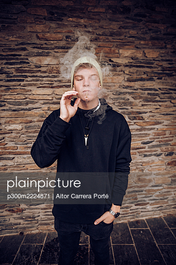Young man smoking with hands in pockets standing against wall - p300m2224871 by Aitor Carrera Porté
