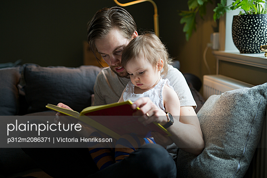 Father reading with son - p312m2086371 by Victoria Henriksson