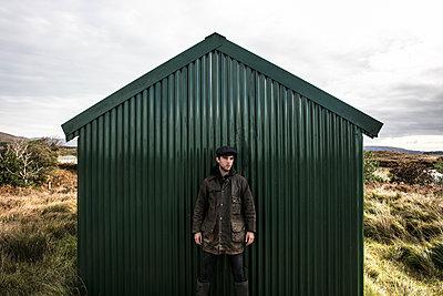 Man in front of a hut - p1082m2022019 by Daniel Allan