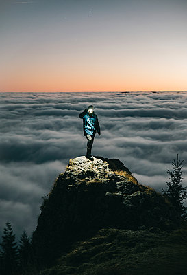 Person Standing on the Mountain Above the Clouds with Flashlight - p1166m2232484 by Cavan Images