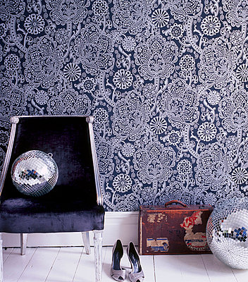 Bold patterned wallpaper in a hallway with upholstered chair shoes suitcase and disco balls - p349m695243 by Emma Lee