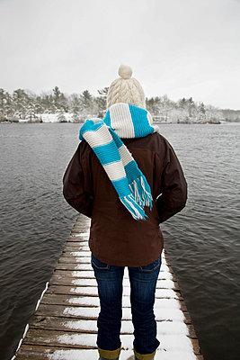 Woman standing on dock in winter - p4297915 by Hugh Whitaker