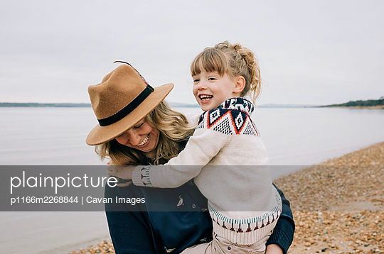 mom and daughter laughing together whilst walking on the beach in fall - p1166m2268844 by Cavan Images