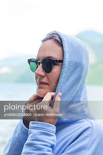 Young woman wearing hoodie - p1609m2253800 by Katrin Wolfmeier
