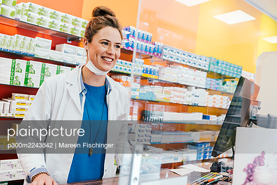 Confident pharmacist with surgical mask standing at checkout counter in chemist shop - p300m2243842 by Mareen Fischinger