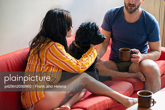 Hipster couple having coffee with pet dog on sofa - p429m2090960 by Frank and Helena