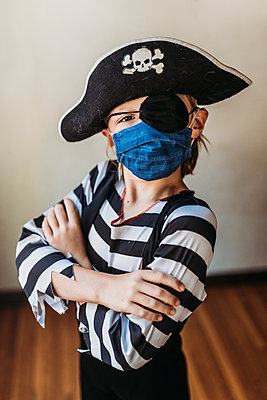 School age young boy dressed as pirate with face mask on - p1166m2207770 by Cavan Images