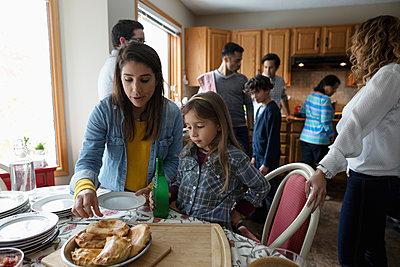 Latinx mother and daughter enjoying fresh empanada - p1192m2034345 by Hero Images