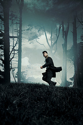 Man in Coat Running on Forest Hill - p1248m2134704 by miguel sobreira