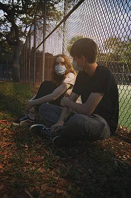 Junges Paar mit Masken an einem Sportplatz - p1694m2291677 von Oksana Wagner