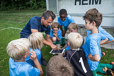 Coach with tablet and young football players on football ground - p300m1581755 by Fotoagentur WESTEND61
