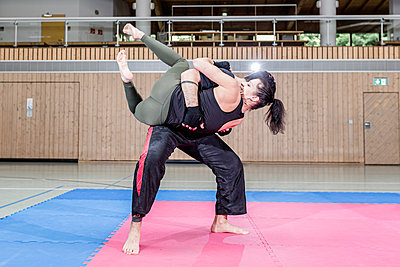 Female kickboxer practising with coach in sports hall - p300m2144525 by Stefanie Baum