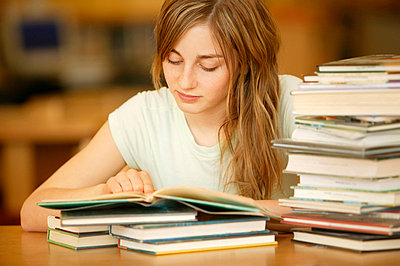Young woman researching through books - p4422876f by Design Pics