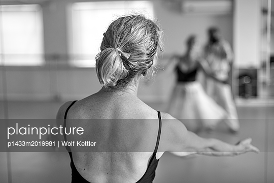 A ballerina with her arms stretched out towards her own and the photographer's reflections in the mirror of the dance studio. - p1433m2019981 by Wolf Kettler
