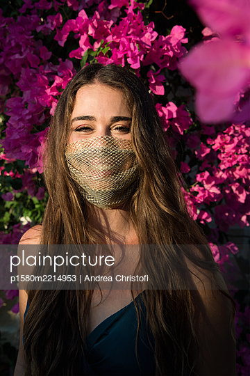Young woman with fashionable mask smiling - p1580m2214953 by Andrea Christofi