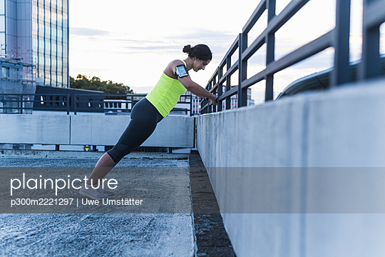 Young woman with arm band exercising on railing at sunset - p300m2221297 by Uwe Umstätter