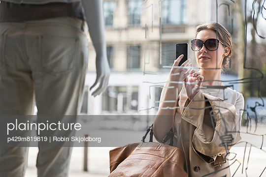 Young woman photographing fashion mannequin outside fashion shop - p429m819819 by Robin Skjoldborg