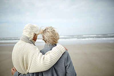 Pensive senior couple hugging and looking at ocean view on windy winter beach - p1023m1402930 by Great Images