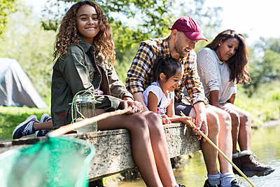 Portrait smiling girl fishing with family on dock - p1023m2066667 by Sam Edwards