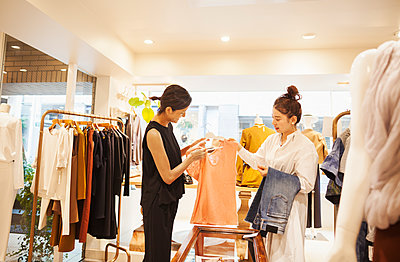 Woman working in a fashion boutique in Tokyo, Japan, serving a customer. - p1100m1185822 by Mint Images