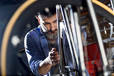 Man working on bicycle in workshop - p300m1562455 by Josep Suria