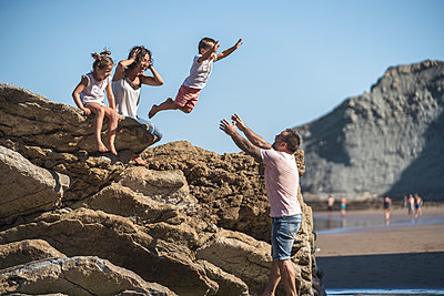 Carefree boy jumping onto father while mother and sister watching at beach - p300m2257268 by SERGIO NIEVAS