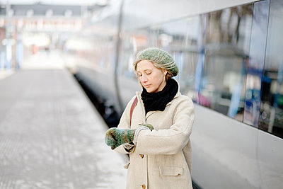 Adult woman checking timebeside train waiting at train station - p312m1551922 by Johner Images