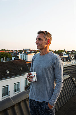 Man holding coffee mug on roof - p341m2008677 by Mikesch