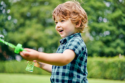 Toddler playing with soap bubbles in park - p429m2164640 by GS Visuals