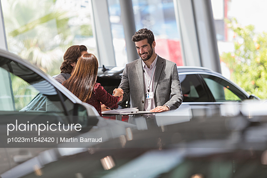 plainpicture | Photo library for authentic images - plainpicture p1023m1542420 - Car salesman handshaking wi... - plainpicture/Caiaimages/Martin Barraud