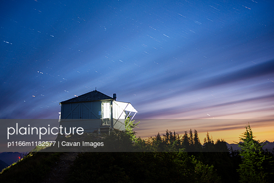 Illuminated cottage on mountain against cloudy sky at night - p1166m1182577 by Cavan Images